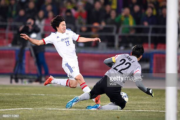 Kwon Chang-hoon of Suwon Samsung FC shoots the ball against goalkeeper Yang Zhi of Beijing Guo'an during the AFC Champions League Group G match...