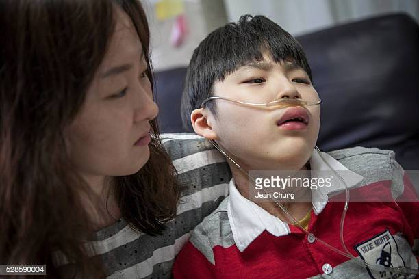 Kwon Miae mother of Lim Seongjoon who is suffering from chronic lung disease comforts him after he was feeling a light nausea while at their home on...