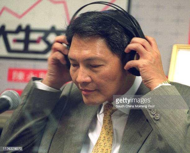 Kwong Ki-chi, Chief Executive of the Hong Kong Exchanges and Clearing , puts on his headphones as he attends a radio programme on Metro Radio at The...
