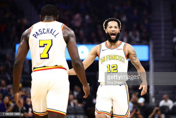 Ky Bowman congratulates Eric Paschall of the Golden State Warriors after he made a basket against the Portland Trail Blazers at Chase Center on...