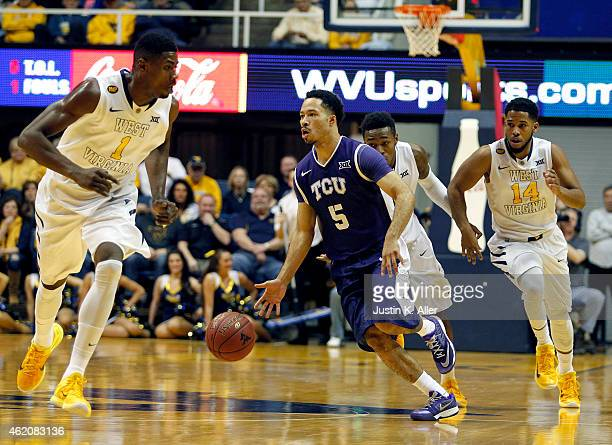 Kyan Anderson of the TCU Horned Frogs brings the ball down court against Jonathan Holton and Gary Browne of the West Virginia Mountaineers during the...