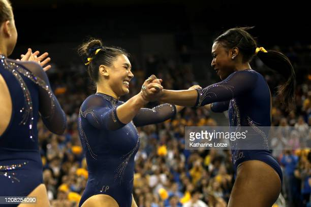 Kyla Ross and Nia Dennis of the UCLA Bruins react following Ross' performance on floor exercise during a meet against the Utah Utes at Pauley...