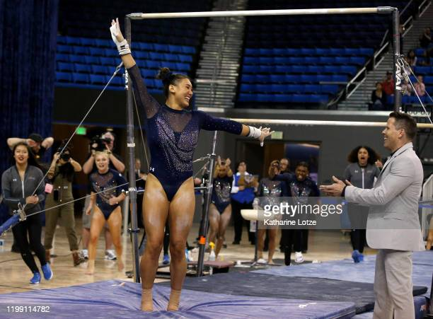 Kyla Ross of UCLA and head coach Chris Waller celebrate after competing on the uneven parallel bars during a meet against Boise State at Pauley...