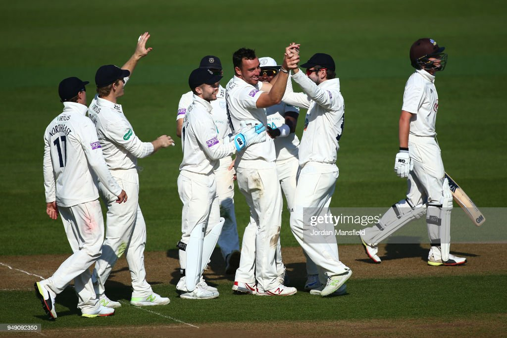 Kyle Abbott of Hampshire celebrates with his teammates after dismissing Ollie Pope of Surrey (R) during day one of the Division One Specsavers County Championship match between Surrey and Hampshire at The Kia Oval on April 20, 2018 in London, England.