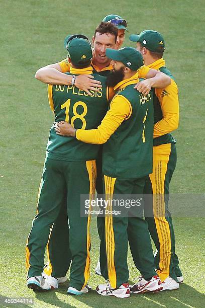 Kyle Abbott of South Africa celebrates with teamates his dismissal of David Warner of Australia during game four of the One Day International series...