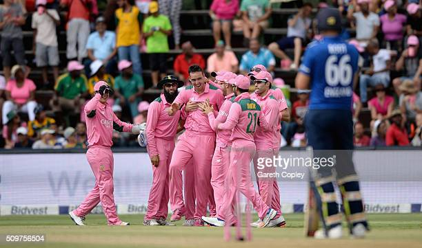 Kyle Abbott of South Africa celebrates with teammates after dismissing Jos Buttler of England during the 4th Momentum ODI between South Africa and...