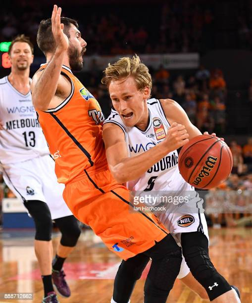 Kyle Adnam of Melbourne United attempts to drive past Jarrad Weeks of the Taipans during the round nine NBL match between the Cairns Taipans and...