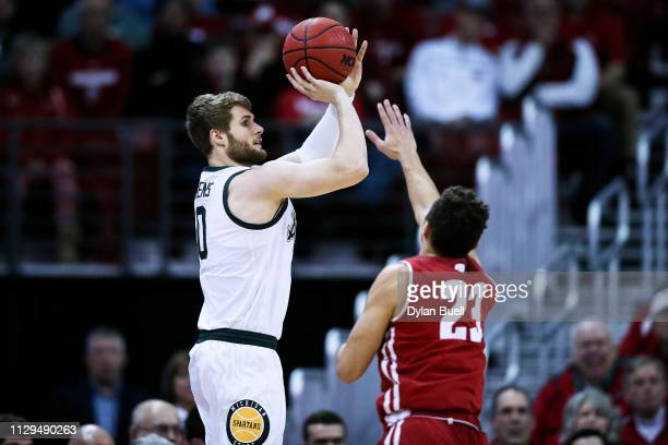 Kyle Ahrens of the Michigan State Spartans attempts a shot while being guarded by Kobe King of the Wisconsin Badgers in the first half at the Kohl...