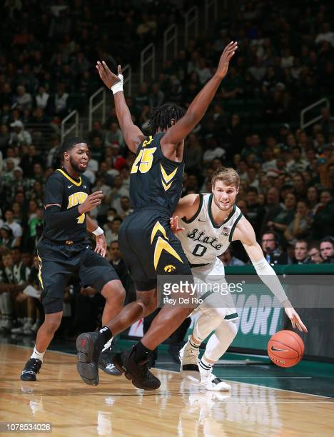 Kyle Ahrens of the Michigan State Spartans drives past Tyler Cook of the Iowa Hawkeyes in the first half at Breslin Center on December 3 2018 in East...