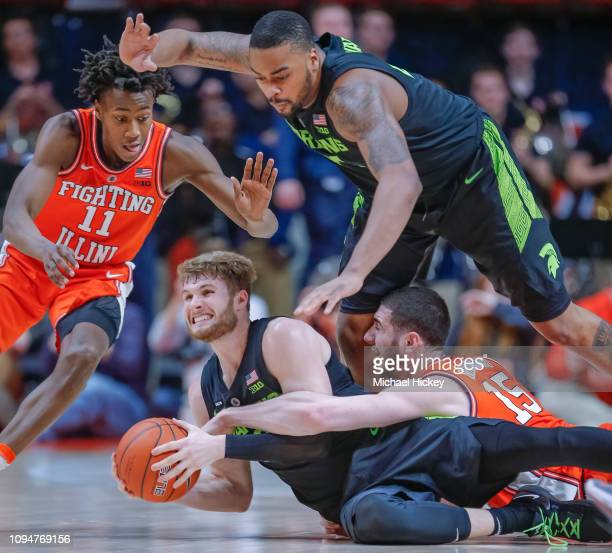 Kyle Ahrens of the Michigan State Spartans fights for ball against Ayo Dosunmu and Giorgi Bezhanishvili of the Illinois Fighting Illini at State Farm...