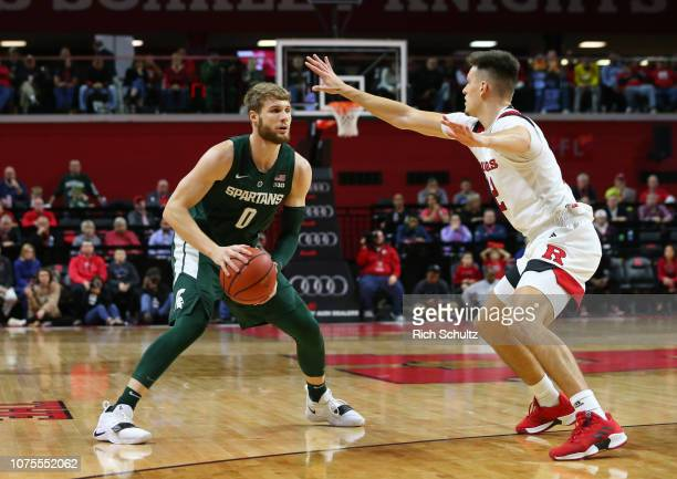 Kyle Ahrens of the Michigan State Spartans in action against Peter Kiss of the Rutgers Scarlet Knights during a college basketball game at the...