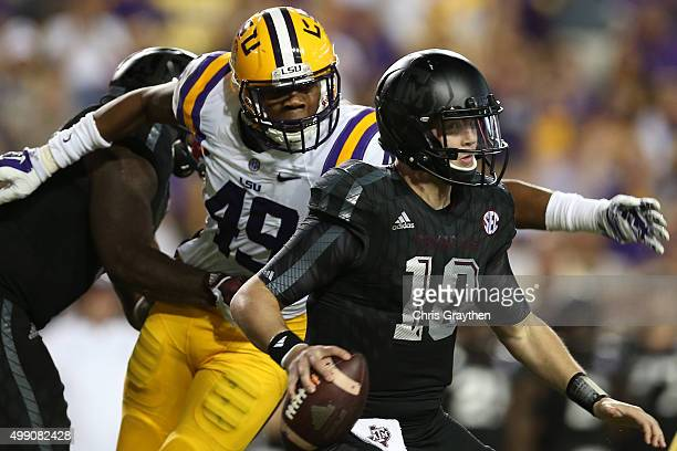 Kyle Allen of the Texas AM Aggies avoids a tackle by Arden Key of the LSU Tigers at Tiger Stadium on November 28 2015 in Baton Rouge Louisiana