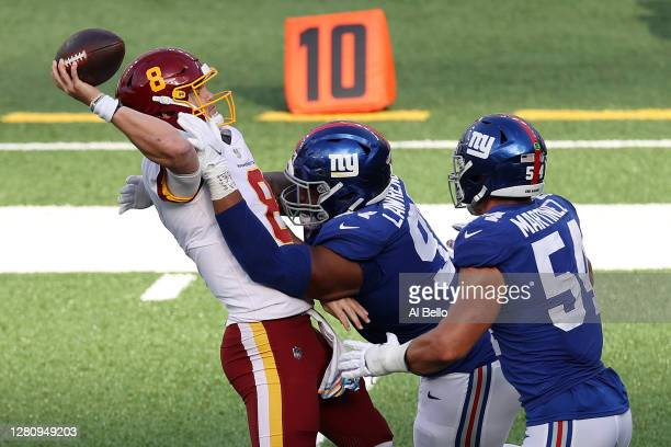 Kyle Allen of the Washington Football Team is hit by Dexter Lawrence of the New York Giants as he is unsuccessful on a two point conversion to take...