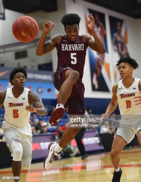 Kyle Allman and Davon Clare of the Cal State Fullerton Titans defend Rio Haskett of the Harvard Crimson as he drives to the basket in the second half...