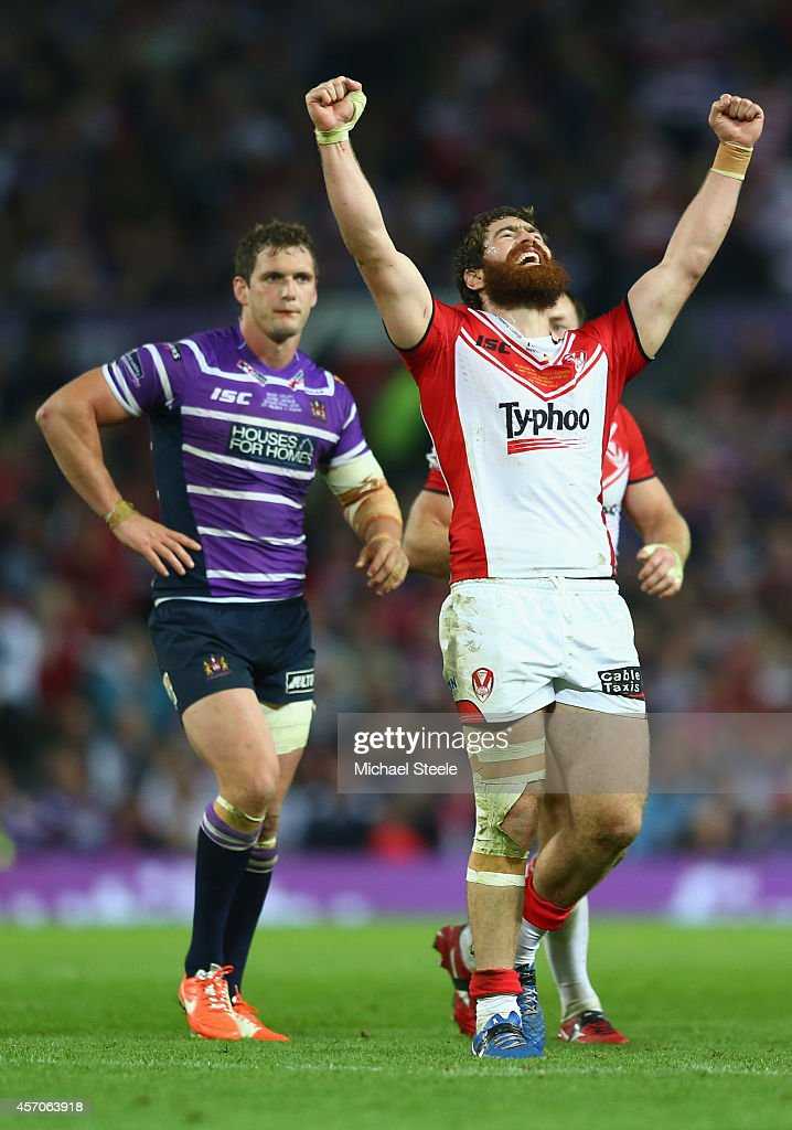Kyle Amor (R) of St Helens celebrates his sides 14-6 victory as Sean O'Loughlin (L) the captain of Wigan looks on dejectedly during the First Utility Super League Grand Final match between St Helens and Wigan Warriors at Old Trafford on October 11, 2014 in Manchester, England.