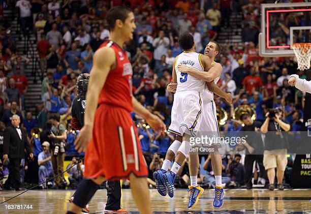 Kyle Anderson and Travis Wear of the UCLA Bruins celebrate as Nick Johnson of the Arizona Wildcats walks by after the Bruins defeat the Wildcats...