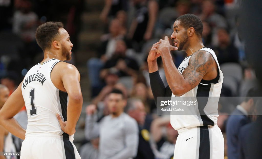 Kyle Anderson #1 of the San Antonio Spurs and LaMarcus Aldridge #12 of the San Antonio Spurs share a light moment during a time-out against the Orlando Magic at AT&T Center on March 13, 2018 in San Antonio, Texas.