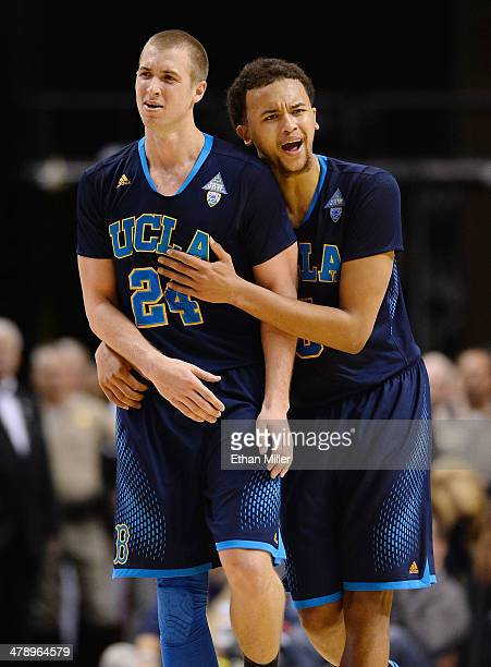 Kyle Anderson of the UCLA Bruins consoles teammate Travis Wear after he fouled out of the championship game of the Pac-12 Basketball Tournament...