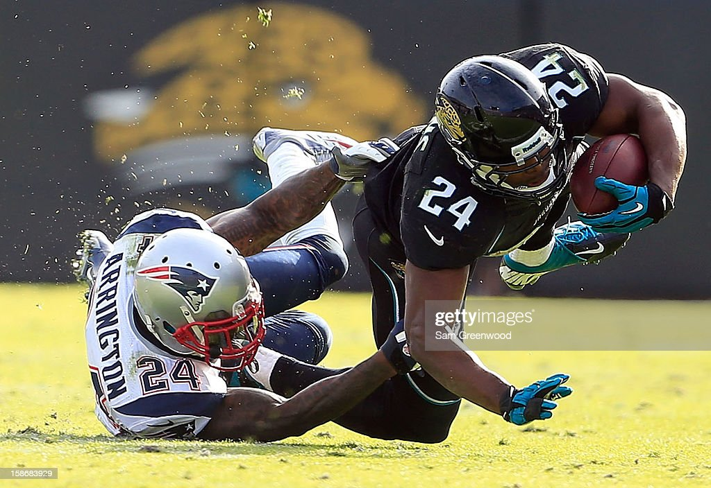 Kyle Arrington #24 of the New England Patriots tackles Montell Owens #24 of the Jacksonville Jaguars during the game at EverBank Field on December 23, 2012 in Jacksonville, Florida.