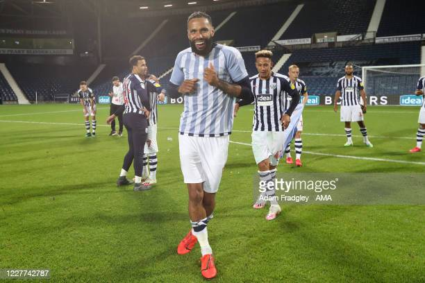 Kyle Bartley and Callum Robinson of West Bromwich Albion dance on the pitch as the team celebrate promotion to the Premier League on the pitch at the...