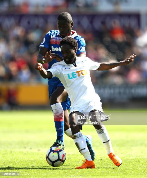 Kyle Bartley of Swansea City battles for possession with Badou Ndiaye of Stoke City during the Premier League match between Swansea City and Stoke...