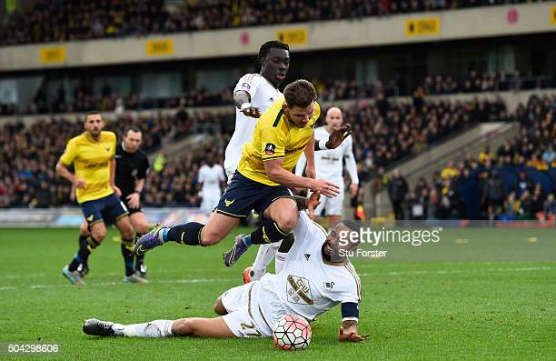 Kyle Bartley of Swansea City brings down Alex MacDonald of Oxford United for a penalty during The Emirates FA Cup third round match between Oxford...