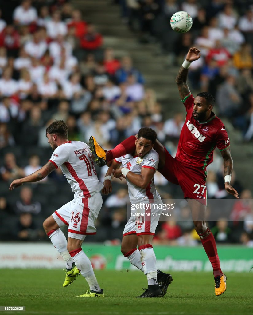 Kyle Bartley of Swansea City goes up for an arial challenge with Robbie Muirhead and Sam Nombe of MK Dons and Bartley is subsequently injured during the Carabao Cup Second Round match between Milton Keynes Dons and Swansea City at StadiumMK on August 22, 2017 in Milton Keynes, England.