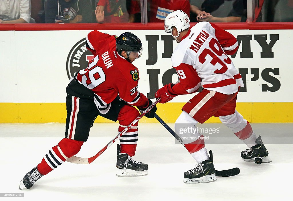 Kyle Baun #39 of the Chicago Blackhawks pokes the puck between the legs of Anthony Mantha #39 of the Detroit Red Wings during a preseason game at the United Center on September 22, 2015 in Chicago, Illinois. The Blackhawks defeated the Red Wings 5-4 in overtime.