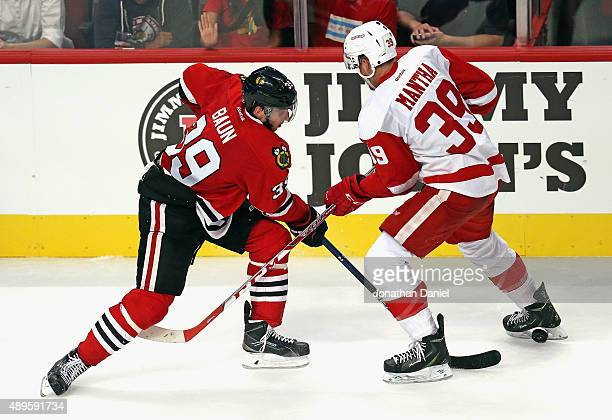 Kyle Baun of the Chicago Blackhawks pokes the puck between the legs of Anthony Mantha of the Detroit Red Wings during a preseason game at the United...