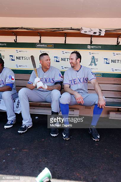 Kyle Blanks and Adam Rosales of the Texas Rangers talk in the dugout prior to the game against the Oakland Athletics at Oco Coliseum on June 11 2015...