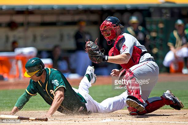 Kyle Blanks of the Oakland Athletics is tagged out at home plate by David Ross of the Boston Red Sox during the second inning at Oco Coliseum on June...