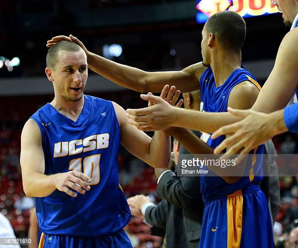 Kyle Boswell of the UC Santa Barbara Gauchos is congratulated as he comes out of the game by teammates on the bench including Taran Brown during...