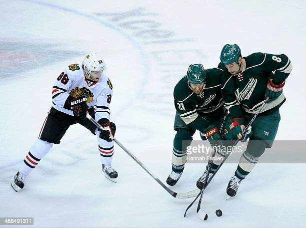 Kyle Brodziak and Cody McCormick of the Minnesota Wild controls the puck against Patrick Kane of the Chicago Blackhawks during the first period in...