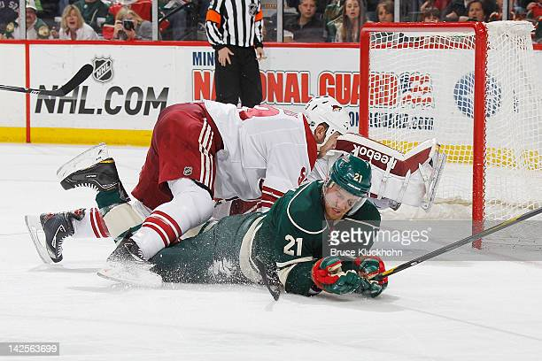 Kyle Brodziak of the Minnesota Wild collides with Derek Morris and goalie Mike Smith of the Phoenix Coyotes on a scoring attempt during the game at...