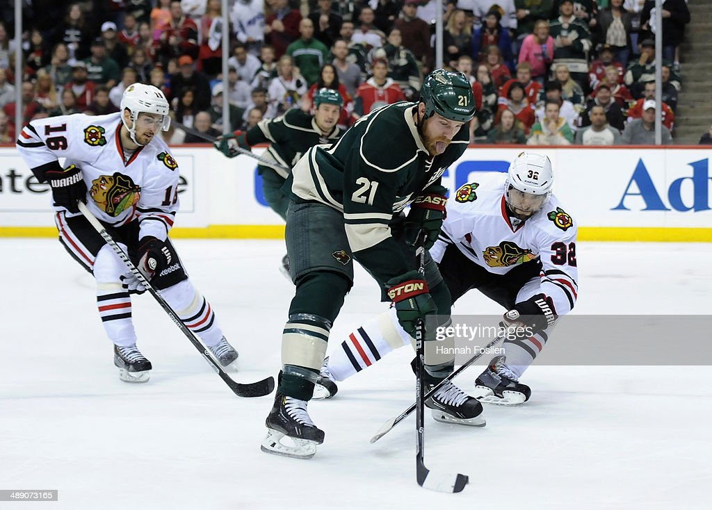 Kyle Brodziak #21 of the Minnesota Wild controls the puck against Marcus Kruger #16 and Michal Rozsival #32 of the Chicago Blackhawks during the second period in Game Four of the Second Round of the 2014 NHL Stanley Cup Playoffs on May 9, 2014 at Xcel Energy Center in St Paul, Minnesota.