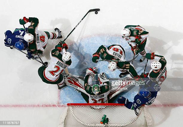 Kyle Brodziak of the Minnesota Wild gathers up a loose puck in front of goaltender Niklas Backstrom of the Minnesota Wild during their game against...