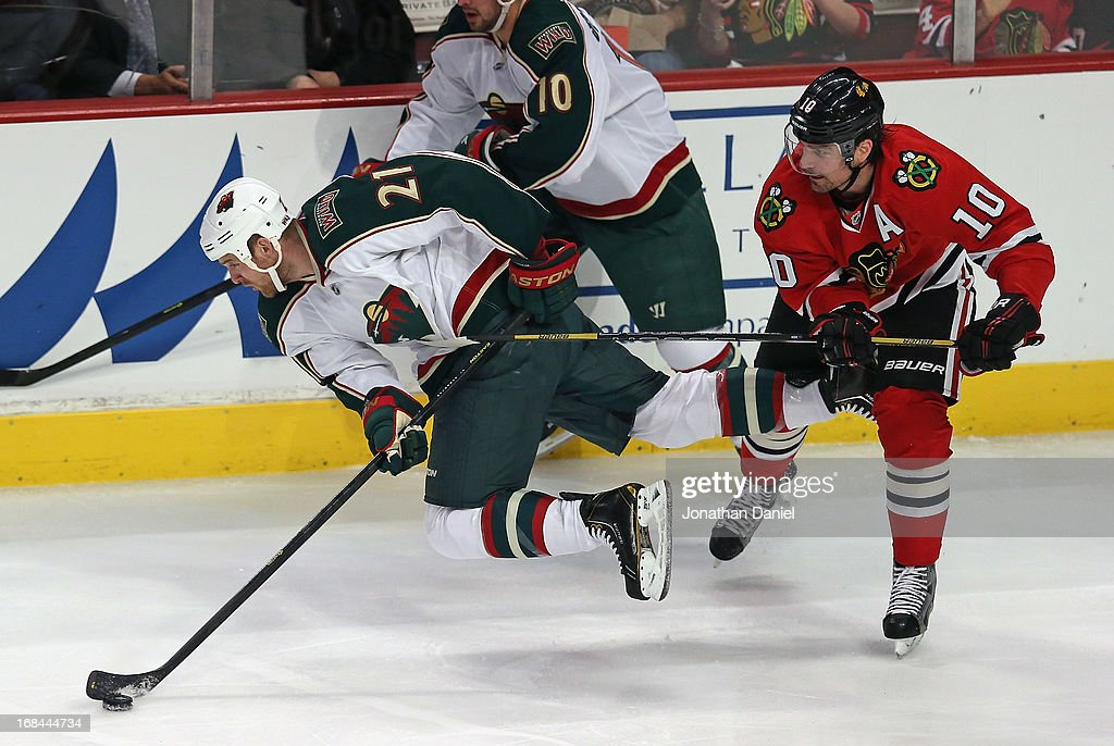 Kyle Brodziak #21 of the Minnesota Wild slips trying to pass the puck under pressure from Patrick Sharp #10 of the Chicago Blackhawks in Game Five of the Western Conference Quarterfinals during the 2013 NHL Stanley Cup Playoffs at the United Center on May 9, 2013 in Chicago, Illinois.