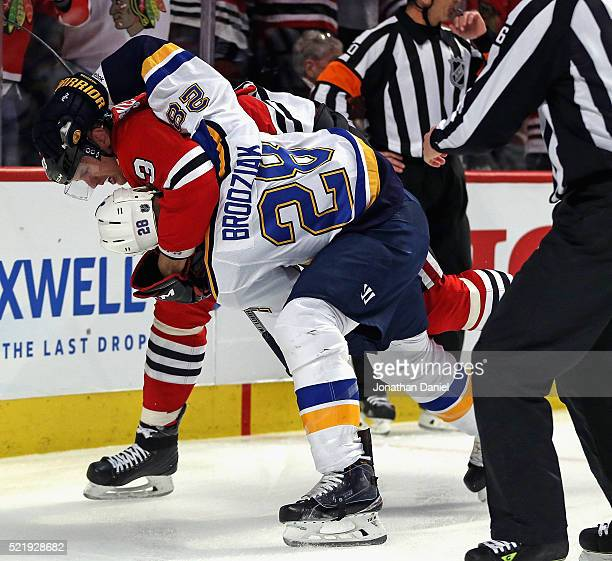 Kyle Brodziak of the St Louis Blues and Viktor Svedberg of the Chicago Blackhawks fight in the first period in Game Three of the Western Conference...