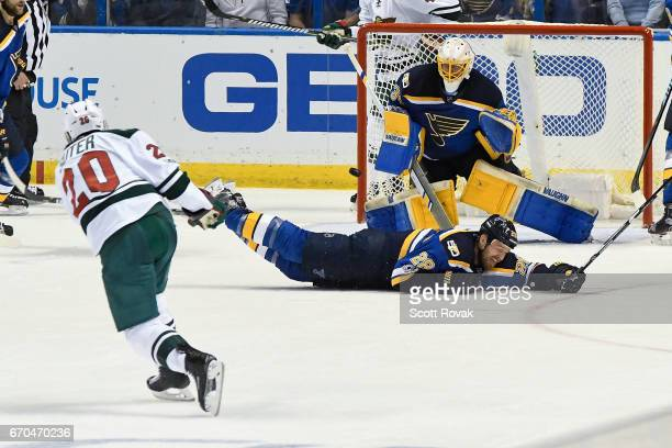 Kyle Brodziak of the St Louis Blues attempts to block a shot by Ryan Suter of the Minnesota Wild as Jake Allen of the St Louis Blues makes the save...
