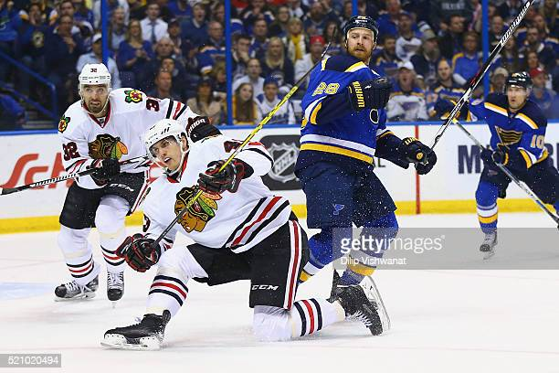 Kyle Brodziak of the St Louis Blues checks Viktor Svedberg of the Chicago Blackhawks in Game One of the Western Conference Quarterfinals during the...