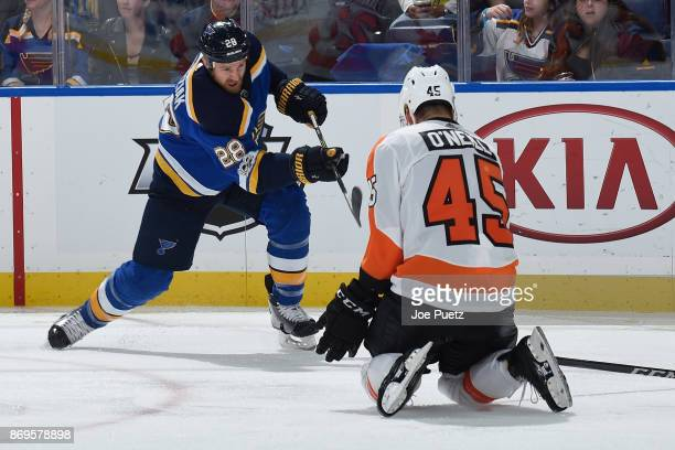 Kyle Brodziak of the St Louis Blues takes a shot as Will O'Neill of the Philadelphia Flyers defends at Scottrade Center on November 2 2017 in St...