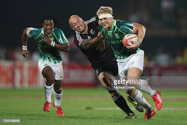 Kyle Brown of South Africa powers his way past DJ Forbes of New Zealand during the South Africa v New Zealand match on Day Two of the IRB Dubai...