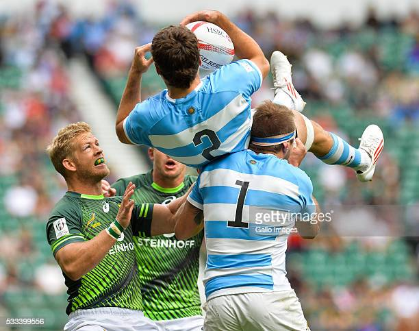 Kyle Brown of South Africa watches as Fernando Luna lifts Santiago Alvarez of Argentina in the air during the cup quarter final match between South...