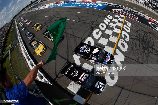 Kyle Busch, driver of the Cessna Toyota, and Todd Gilliland, driver of the Mobil 1 Toyota, lead the field to the green flag to start the NASCAR...