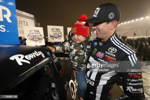 Kyle Busch driver of the Cessna Toyota celebrates with his son Brexton by placing the Winner's sticker on his car after winning the NASCAR Gander...