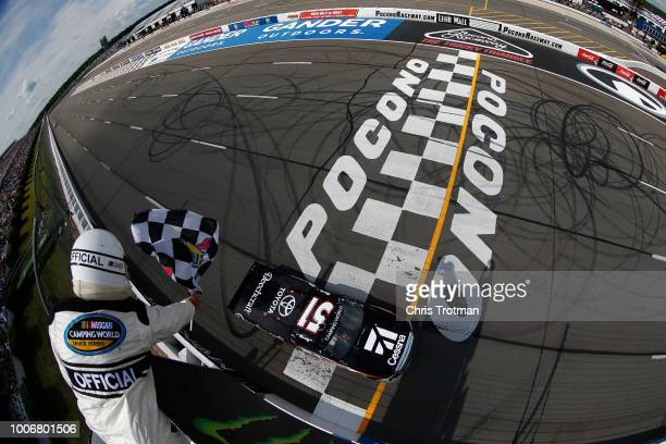 Kyle Busch driver of the Cessna Toyota crosses the finish line to win the NASCAR Camping World Truck Series Gander Outdoors 150 at Pocono Raceway on...
