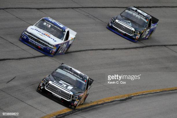 Kyle Busch driver of the Cessna Toyota leads Johnny Sauter driver of the Allegiant Airlines Chevrolet and Brett Moffitt driver of the AISIN Toyota...