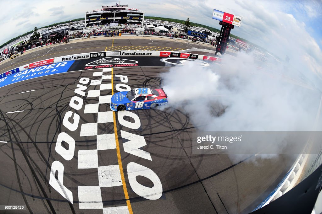 Kyle Busch, driver of the #18 Comcast Salute to Service/Juniper Toyota, celebrates with a burnout after winning the NASCAR Xfinity Series Pocono Green 250 Recycled by J.P. Mascaro & Sons at Pocono Raceway on June 2, 2018 in Long Pond, Pennsylvania.