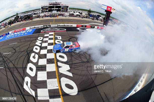 Kyle Busch driver of the Comcast Salute to Service/Juniper Toyota celebrates with a burnout after winning the NASCAR Xfinity Series Pocono Green 250...