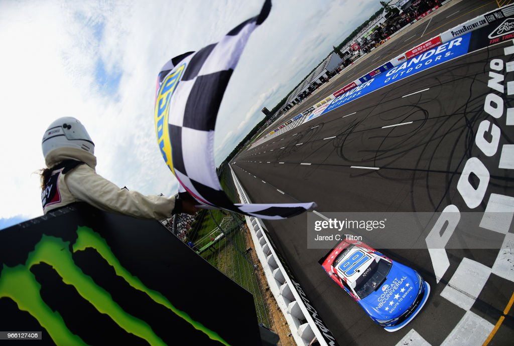 Kyle Busch, driver of the #18 Comcast Salute to Service/Juniper Toyota, takes the checkered flag to win the NASCAR Xfinity Series Pocono Green 250 Recycled by J.P. Mascaro & Sons at Pocono Raceway on June 2, 2018 in Long Pond, Pennsylvania.